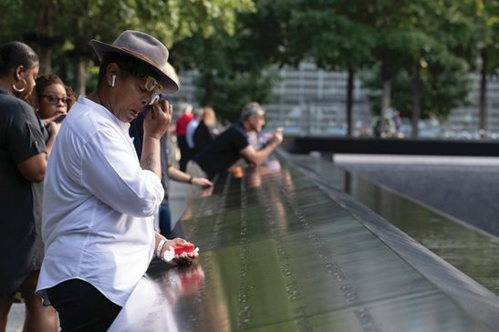 A woman wipes away tears as she stands next to the north pool prior to a ceremony marking the 18th anniversary of the attacks of Sept. 11, 2001 at the National September 11 Memorial Wednesday morning in New York.