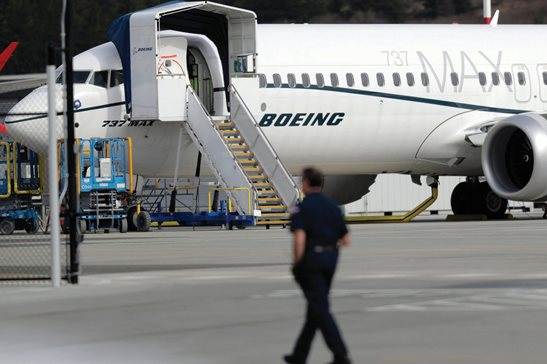 A worker walks next to a Boeing 737 MAX 8 airplane parked at Boeing Field in Seattle in March. Boeing said Thursday it will take a $4.9 billion charge to cover possible compensation to airlines whose Max jets remain grounded after two deadly accidents. The charge does not include amounts Boeing may pay in dozens of lawsuits filed by families of crash victims. Boeing this week hired a victims-compensation expert to oversee a $50 million relief fund separate from the lawsuits.