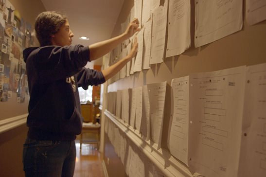 "Journalist and filmmaker Assia Boundaoui hangs FBI documents in a frame from her 2018 documentary, ""The Feeling of Being Watched,"" about federal surveillance of Bridgeview's Muslim community. A federal judge last week directed the FBI to process 1,000 pages a month of Operation Vulgar Betrayal documents sought by Boundaoui under the Freedom of Information Act."