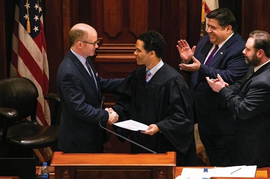Newly sworn-in Illinois Senate President Don Harmon, D-Oak Park, left, shakes hands with 7th Circuit Associate Judge Rudolph M. Braud Jr. after taking the oath of office, along with Gov. J.B. Pritzker, second from right, in the Illinois Senate at the Illinois State Capitol Sunday.