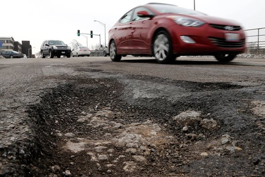 Motorists dodge one of Chicago's infamous potholes in a 2014 file photo. A split 1st District panel last week affirmed the dismissal of a suit brought by a woman who tripped in a Northwest Side pothole outside her car. Why? Because the car was illegally parked near a fire hydrant.