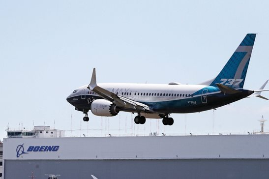 A Boeing 737 MAX jet heads to a landing at Boeing Field following a test flight Monday in Seattle. The Federal Aviation Administration test flights this week will evaluate Boeing's proposed changes to the automated flight control system on the MAX, a system that activated erroneously on two flights that crashed, killing 346 people.