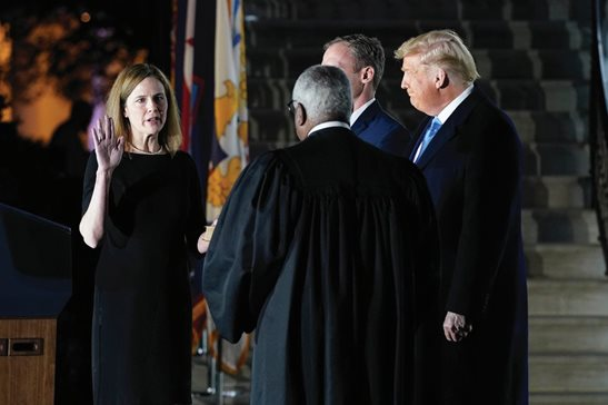 Amy Coney Barrett takes her constitutional oath for the Supreme Court, administered by associate justice Clarence Thomas, Monday night on the South Lawn of the White House as President Donald Trump looks on. Barrett was confirmed to the nation's high court by the Senate earlier Monday by a 52-48 vote.