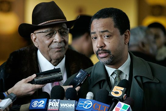 In his trademark black hat, Justice R. Eugene Pincham (left) returned to practice after stepping down from the bench in 1989. In this Dec. 19, 2005, Associated Press photo, Pincham faces reporters with his client Dwain Kyles, right, owner of the E2 nightclub where a 2003 stampede killed 21 people.