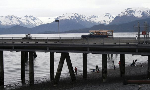 In this file photo from May 2015, a vehicle drives on a pier to be loaded onto an Alaska state ferry while people fish underneath the pier in Homer, Alaska. The U.S. Supreme Court will hear oral arguments Monday in a case that will determine who is eligible to receive more than $530 million in federal virus relief funding set aside for tribes more than a year ago. More than a dozen Native American tribes sued the U.S. Treasury Department to keep the money out of the hands of Alaska Native corporations, which provide services to Alaska Natives but do not have a government-to-government relationship with the United States.