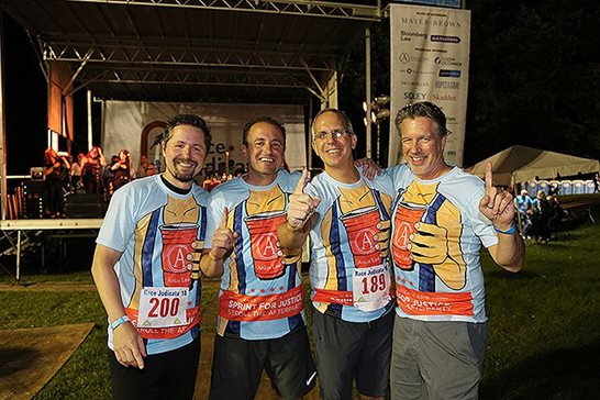 Members of Ankin Law Office's Race Judicata delegation show off their contest-winning T-shirts at the race's afterparty on Sept. 13 in Lincoln Park. The firm's founder, Howard H. Ankin (second from right), said winning the design competition at the fundraiser was a longtime career goal.