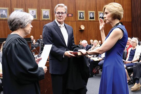 Chief U.S. District Judge Rebecca R. Pallmeyer is sworn in Monday as the top jurist on Chicago's federal trial court while her husband, Dan P. McAdams, holds the Bible. Chief Judge Diane P. Wood of the 7th U.S. Circuit Court of Appeals administered the oath. Pallmeyer and Wood are the first women to lead their respective courts.
