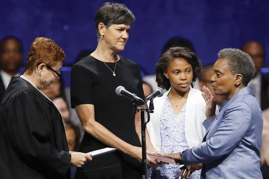 Mayor Lori Lightfoot (right) takes her oath from U.S. Magistrate Judge Susan E. Cox (left) as her spouse Amy Eshleman (second left) and her daughter Vivian look during her inauguration ceremony Monday. Cox and Lightfoot worked together as assistant U.S. attorneys earlier in their careers and remain close friends.