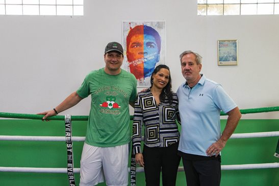 Attorney John W. Chwarzynski Jr., Jamillah Ali, and attorney Mike Joyce stand in front of a Richard Slone painting of Jamillah's father and Joyce's father-in-law, boxing legend Muhammed Ali. The painting has been made into a nonfungible token to be auctioned off to the highest bidder via online platform SuperRare. The money from the auction will be split between Joyce's Celtic Boxing Club, the boxing program Leo High School, and a currently undecided charity supporting Parkinson's Disease research.