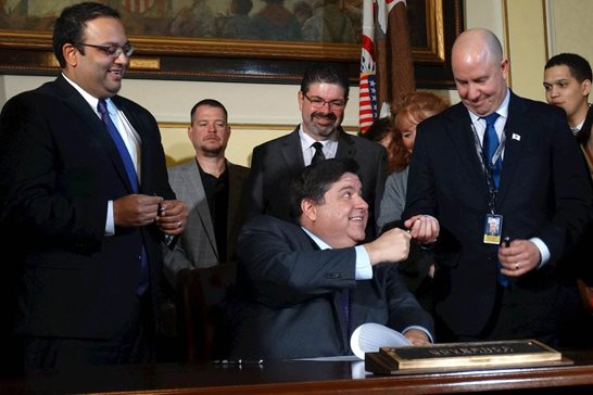 Gov. J.B. Pritzker hands a pen to Rep. Lance Yednock, D-Ottawa, after signing a bill that prohibits local governments in Illinois from enacting right-to-work ordinances. Also at the bill signing ceremony Friday was Sen. Ram Villivalam (left), a Chicago Democrat who was lead sponsor of the bill in the Senate.