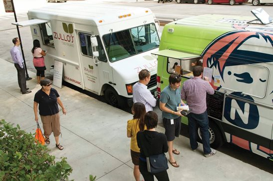 Food trucks line up to serve customers and gather petition signatures in this July 2012 photo, taken days before the Chicago City Council passed an ordinance restricting the trucks from parking within 200 feet of restaurants. That ordinance was upheld by the Illinois Supreme Court Thursday, after finding the food truck regulations were not unconstitutional. AP Photo/Sitthixay Ditthavong