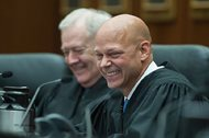 Newly sworn-in Magistrate Judge M. David Weisman reacts as the accolades and jokes come from four speakers at his investiture Thursday at the Dirksen Federal Courthouse. Sitting next to Weisman is Magistrate Judge Michael T. Mason.